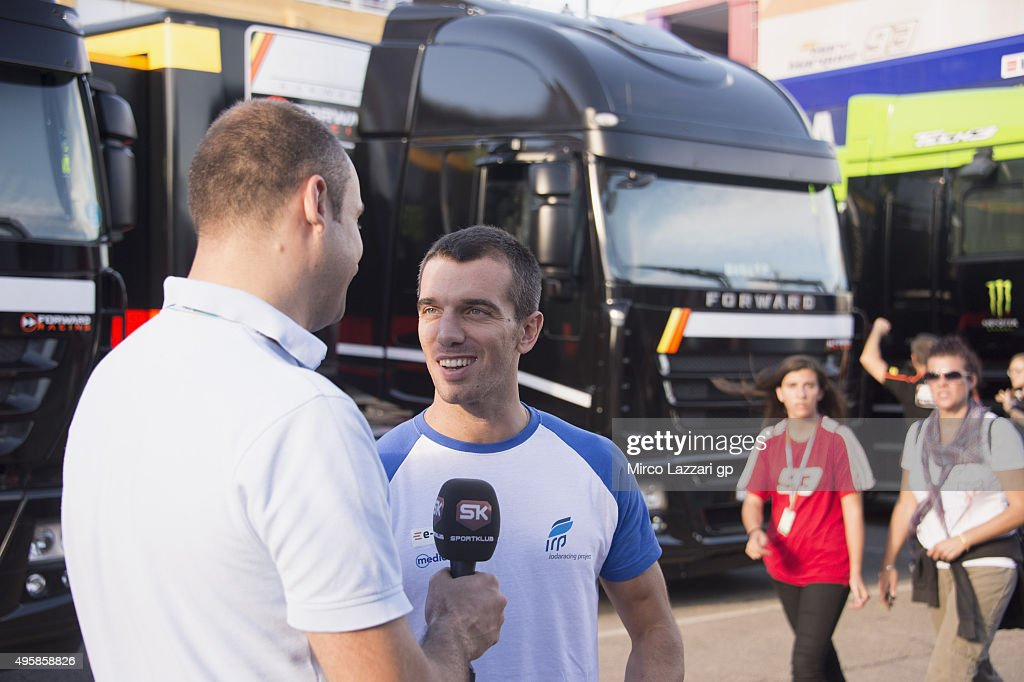 Alex De Angelis of San Marino and E-Motion Iodaracing Team smiles in paddock with a journalist (first time in circuit after the crash in Motegi GP) during the MotoGP of Valencia - Previews at Ricardo Tormo Circuit on November 5, 2015 in Valencia, Spain.