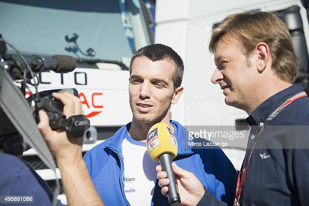Alex De Angelis of San Marino and EMotion Iodaracing Team speaks in paddock with a journalist during the MotoGP of Valencia Previews at Ricardo Tormo...