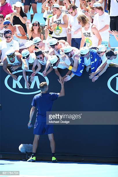 Alex De Minaur of Australia celebrates winning his first round match against Gerald Melzer of Austria with fans on day one of the 2017 Australian...