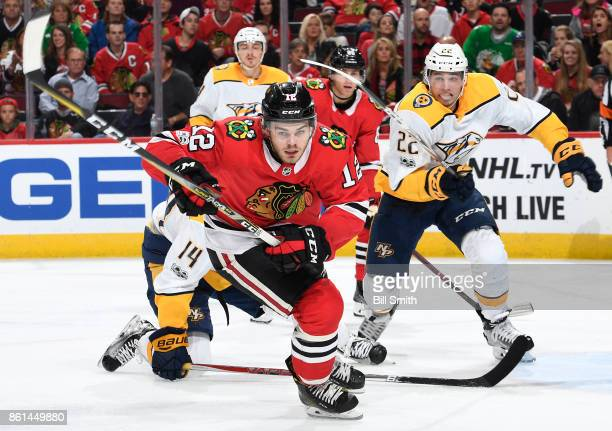 Alex DeBrincat of the Chicago Blackhawks and Kevin Fiala of the Nashville Predators skate in the third period at the United Center on October 14 2017...