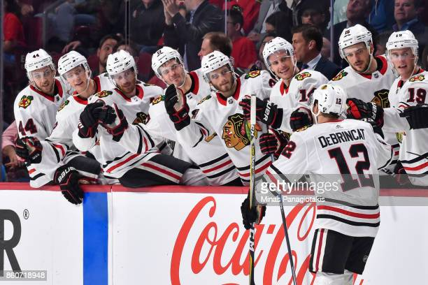 Alex DeBrincat of the Chicago Blackhawks celebrates a first period goal with teammates on the bench against the Montreal Canadiens during the NHL...