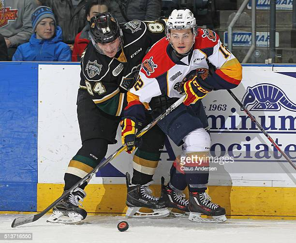 Alex DeBrincat of the Erie Otters battles against JJ Piccinich of the London Knights during an OHL game at Budweiser Gardens on March 3 2016 in...