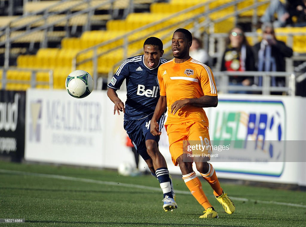 Alex Dixon #19 of the Houston Dynamo heads upfield as Ethen Sampson #43 of the Vancouver Whitecaps FC defends during the first half of a game on February 20, 2013 in Charleston, North Carolina.