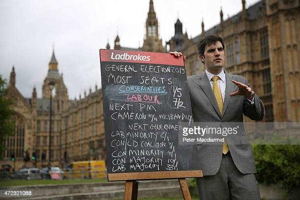 Alex Donohue from Ladbrokes displays election betting odds on a blackboard near Parliament on May 6 2015 in London England Britain's political...