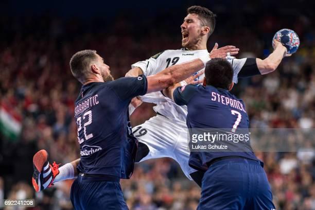 Alex Dujshebaev of Vardar is attacked by Luka Karabatic and Luka Stepancic of Paris during the VELUX EHF FINAL4 Final match between Paris...