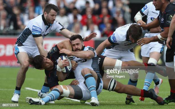 Alex Dunbar of Glagsow is tackled by Michael Rhodes during the European Rugby Champions Cup match between Saracens and Glasgow Warriors at the...