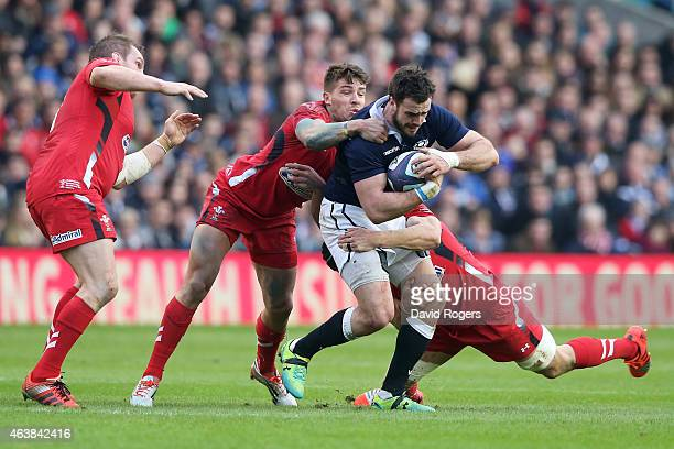 Alex Dunbar of Scotland is tackled by Rhys Webb of Wales and Sam Warburton of Wales during the RBS Six Nations match between Scotland and Wales at...