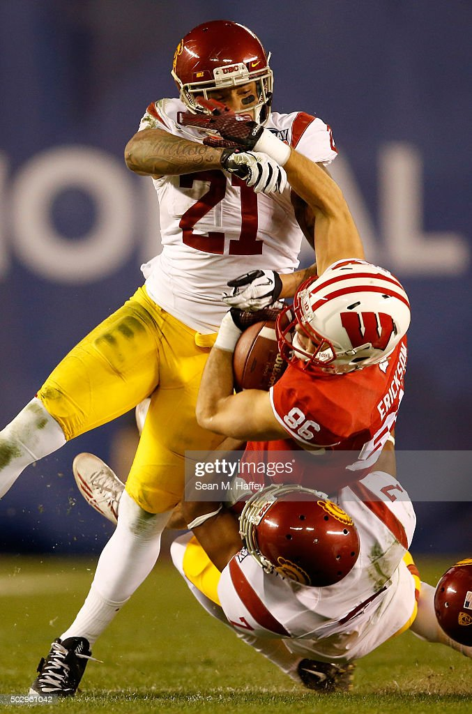 Alex Erickson #86 of the Wisconsin Badgers is wrapped up by Su'a Cravens #21 of the USC Trojans and Marvell Tell III #7 of the USC Trojans during the second quarter of the National University Holiday Bowl at Qualcomm Stadium on December 30, 2015 in San Diego, California.