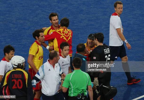 Alex Fabregas of Spain is kept away from match referee John Wright of South Africa during the Men's Hockey match between Great Britain and Spain on...