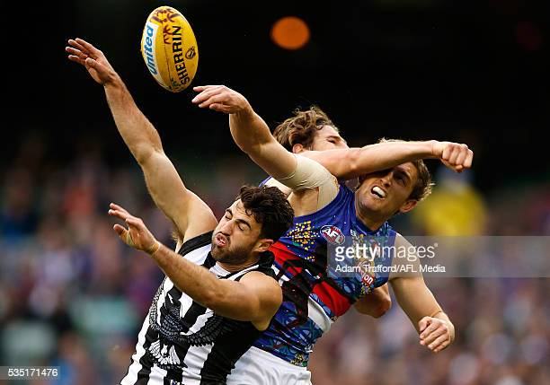 Alex Fasolo of the Magpies competes for the ball with Fletcher Roberts and Marcus Bontempelli of the Bulldogs during the 2016 AFL Round 10 match...