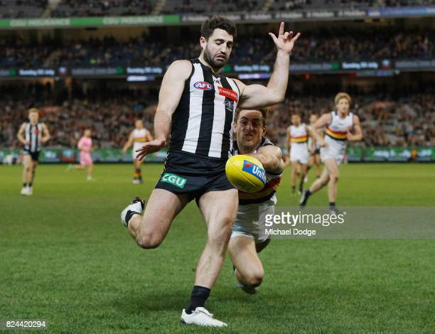 Alex Fasolo of the Magpies kicks the ball away from Richard Douglas of the Crows during the round 19 AFL match between the Collingwood Magpies and...