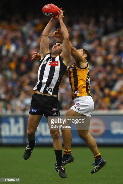 Alex Fasolo of the Magpies marks infront of Paul Puopolo of the Hawks during the round 15 AFL match between the Collingwood Magpies and the Hawthorn...