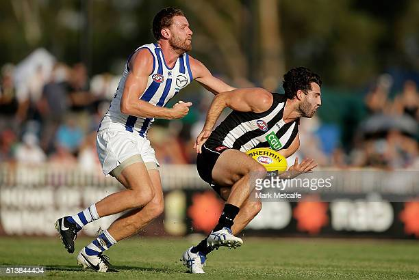 Alex Fasolo of the Magpies marks the ball one handed ahead of Lachlan Hansen of the Kangaroos during the 2016 AFL NAB Challenge match between the...