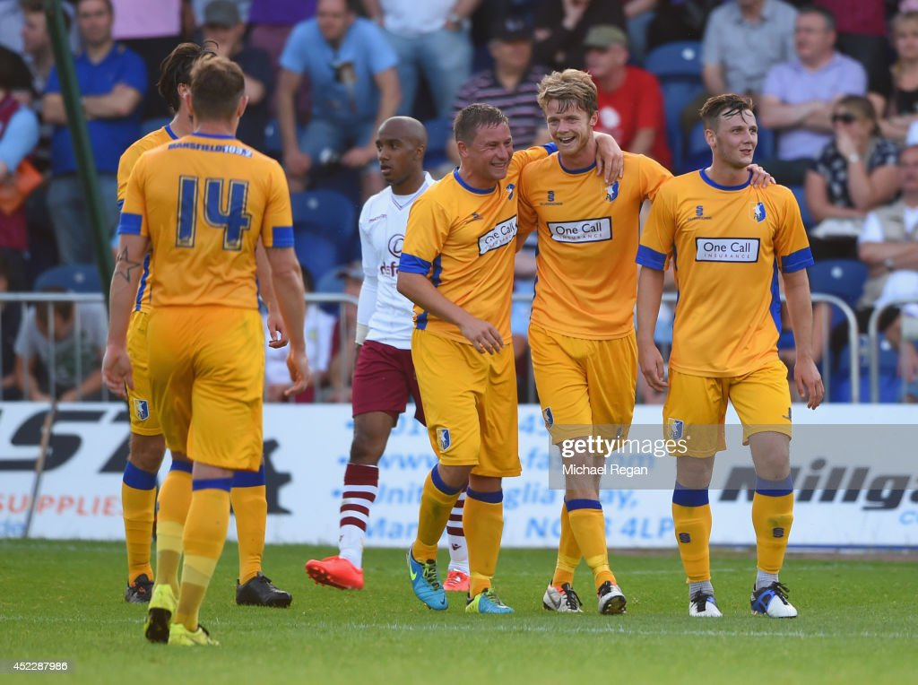 Alex Fisher (c) of Mansfield Town celebrates with team mates after scoring to make it 1-0 during the pre-season friendly match between Mansfield and Aston Villa at the One Call Stadium on July 17, 2014 in Mansfield, England.