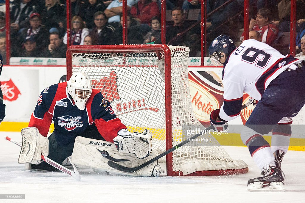 Alex Fotinos #30 of the Windsor Spitfires defends against Justin Kea #9 of the Saginaw Spirit on March 6, 2014 at the WFCU Centre in Windsor, Ontario, Canada.