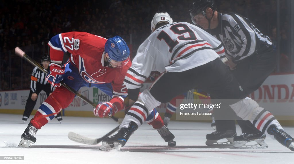 Alex Galchenyuk #27 of the Montreal Canadiens and Jonathan Toews #19 of the Chicago Blackhawks face off in the NHL game at the Bell Centre on March 14, 2017 in Montreal, Quebec, Canada.