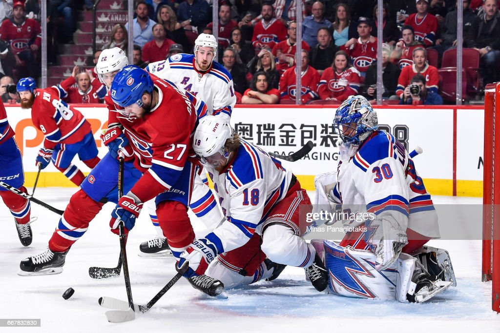 Alex Galchenyuk #27 of the Montreal Canadiens and Marc Staal #18 of the New York Rangers battle for the puck in front of Rangers goaltender Henrik Lundqvist #30 in Game One of the Eastern Conference First Round during the 2017 NHL Stanley Cup Playoffs at the Bell Centre on April 12, 2017 in Montreal, Quebec, Canada.