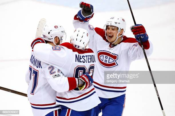 Alex Galchenyuk of the Montreal Canadiens celebrates his overtime goal with Nikita Nesterov and Artturi Lehkonen to defeat the Detroit Red Wings 32...
