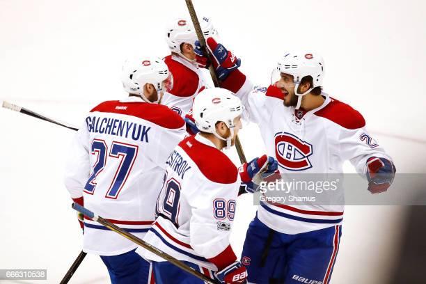 Alex Galchenyuk of the Montreal Canadiens celebrates his overtime goal with Nikita Nesterov Phillip Danault and Artturi Lehkonen to defeat the...