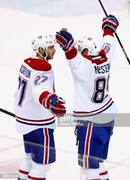 Alex Galchenyuk of the Montreal Canadiens celebrates his overtime goal with Nikita Nesterov to defeat the Detroit Red Wings 32 at Joe Louis Arena on...