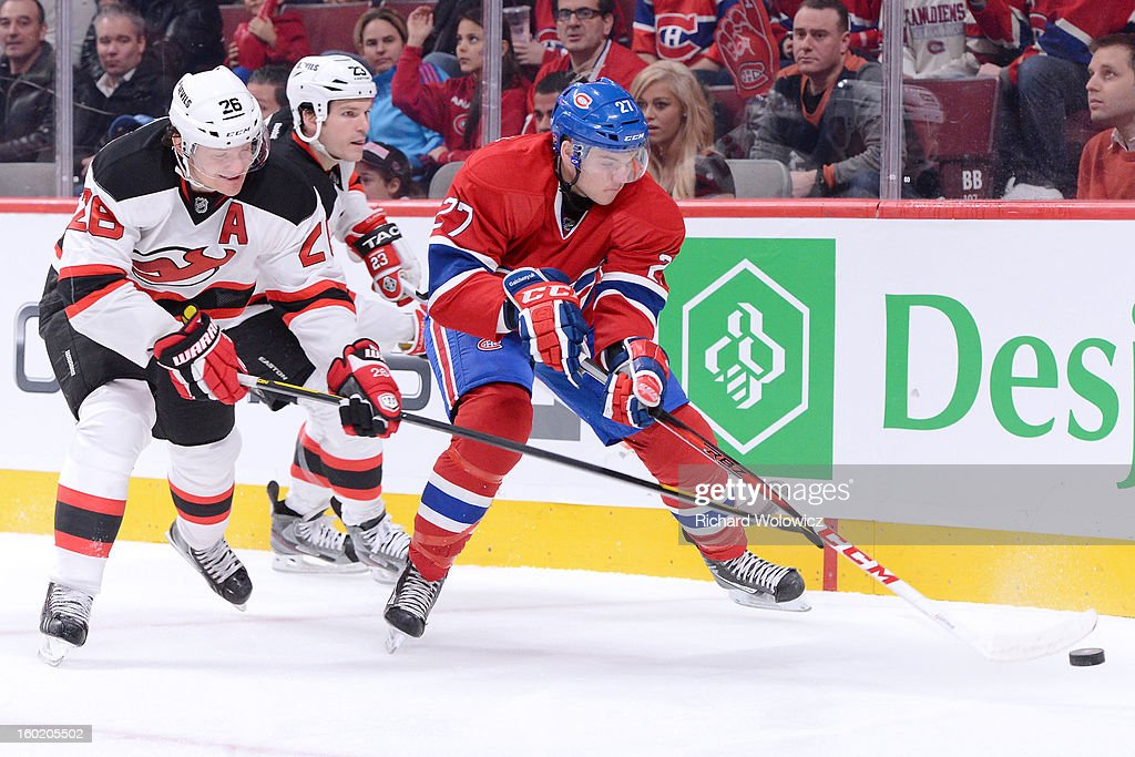 Alex Galchenyuk #27 of the Montreal Canadiens clears the puck from in front of Patrik Elias #26 of the New Jersey Devils during the NHL game at the Bell Centre on January 27, 2013 in Montreal, Quebec, Canada.