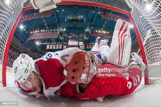 Alex Galchenyuk of the Montreal Canadiens crashes into goaltender Petr Mrazek of the Detroit Red Wings during an NHL game at Joe Louis Arena on April...