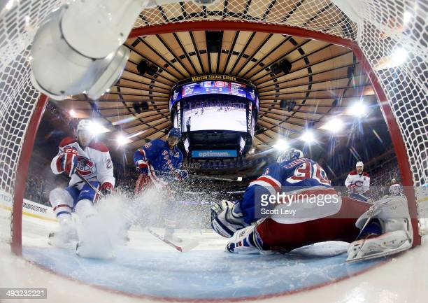 Alex Galchenyuk of the Montreal Canadiens deflects a shot on goal past Henrik Lundqvist of the New York Rangers in the overtime period of Game Three...