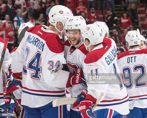 Alex Galchenyuk of the Montreal Canadiens is congratulated following his overtime goal by teammates Michael McCarron and Brendan Gallagher following...