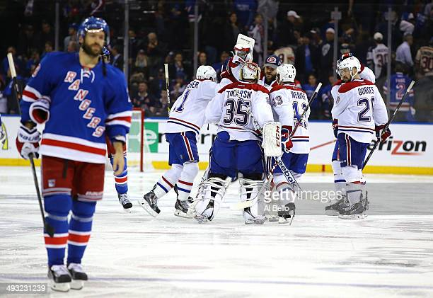 Alex Galchenyuk of the Montreal Canadiens is mobbed by his teammates after scoring the game winning overtime goal as Dominic Moore of the New York...
