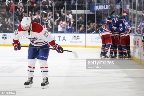 Alex Galchenyuk of the Montreal Canadiens looks on as members of the New York Rangers celebrate an empty net goal in the third period in Game Six of...