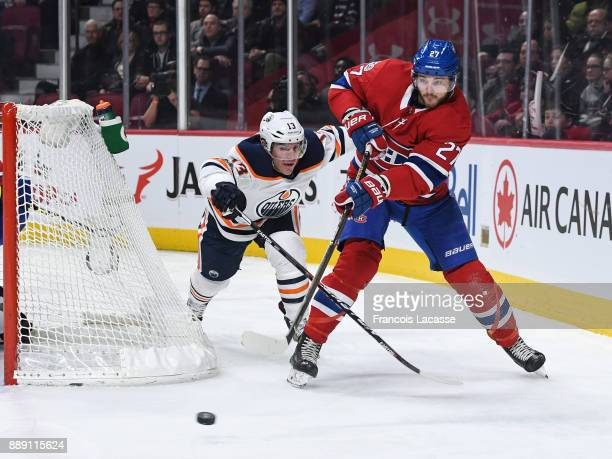 Alex Galchenyuk of the Montreal Canadiens makes a pass while being challenged by Michael Cammalleri of the Edmonton Oilers in the NHL game at the...