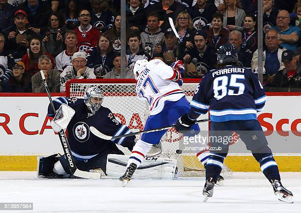 Alex Galchenyuk of the Montreal Canadiens shoots the puck over the outstretched pad of goaltender Ondrej Pavelec of the Winnipeg Jets for a second...