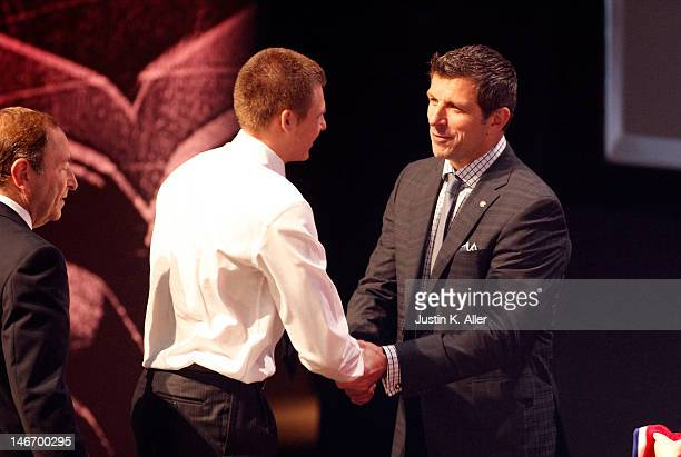 Alex Galchenyuk third overall pick by the Montreal Canadiens shakes hands with general manager Marc Bergevin on stage during Round One of the 2012...
