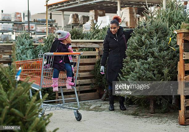 Alex Garcia right shops for a Christmas tree with her daughter Femi Garcia at a Home Depot Inc in Newark New Jersey US on Saturday Dec 10 2011 Sales...