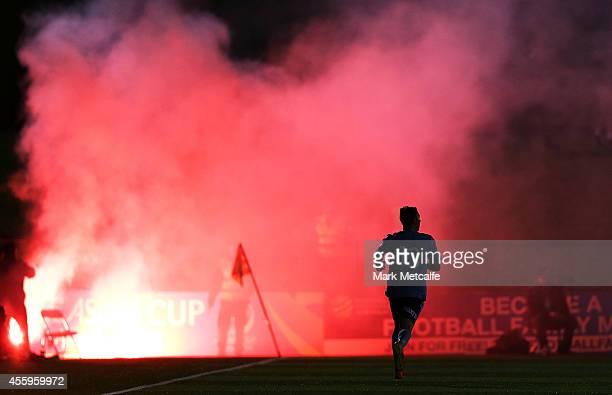Alex Gersbach of Sydney runs towards a cloud of smoke created by a flare during the FFA Cup match between Sydney United 58 FC and Sydney FC at...