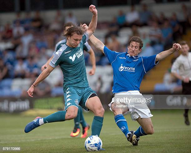 Alex Gilby of Wigan Athletic is tackled by George Pilkington during the PreSeason Friendly between Macclesfield Town and Wigan Athletic at Moss Rose...
