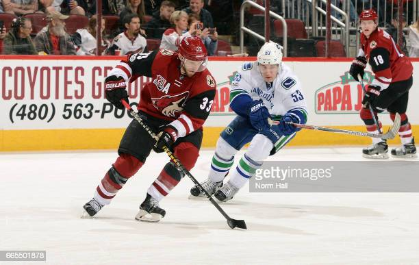 Alex Goligoski of the Arizona Coyotes skates with the puck ahead of Bo Horvat of the Vancouver Canucks during the second period at Gila River Arena...