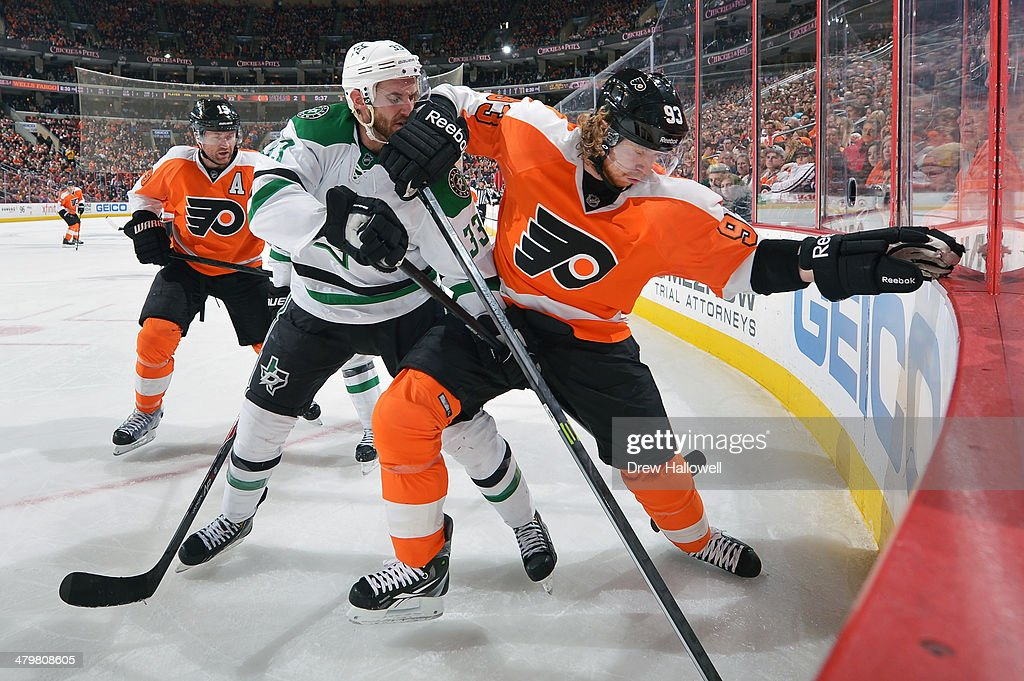 Alex Goligoski of the Dallas Stars and Jakub Voracek of the Philadelphia Flyers battle in the corner for the puck at the Wells Fargo Center on March...