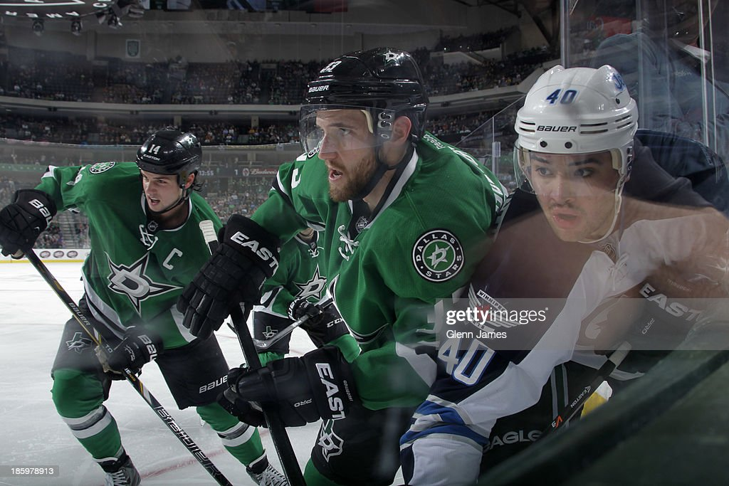 Alex Goligoski #33 of the Dallas Stars levies a check against Devin Setoguchi #40 of the Winnipeg Jets at the American Airlines Center on October 26, 2013 in Dallas, Texas.