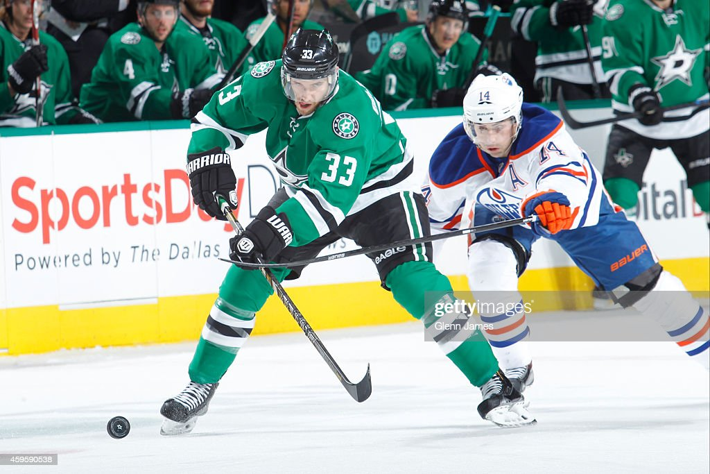 Alex Goligoski of the Dallas Stars tries to keep the puck away against Jordan Eberle of the Edmonton Oilers at the American Airlines Center on...