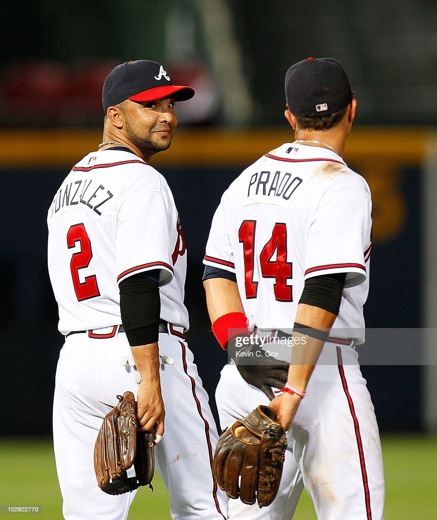 Alex Gonzalez #2 and <a gi-track='captionPersonalityLinkClicked' href=/galleries/search?phrase=Martin+Prado&family=editorial&specificpeople=620159 ng-click='$event.stopPropagation()'>Martin Prado</a> #14 of the Atlanta Braves converse during a pitching change against the Milwaukee Brewers at Turner Field on July 15, 2010 in Atlanta, Georgia.