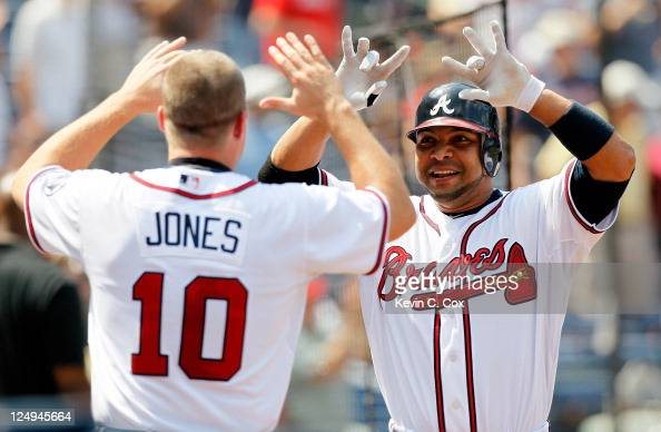 Alex Gonzalez of the Atlanta Braves celebrates his threerun homer with Chipper Jones in the seventh inning against the Florida Marlins at Turner...