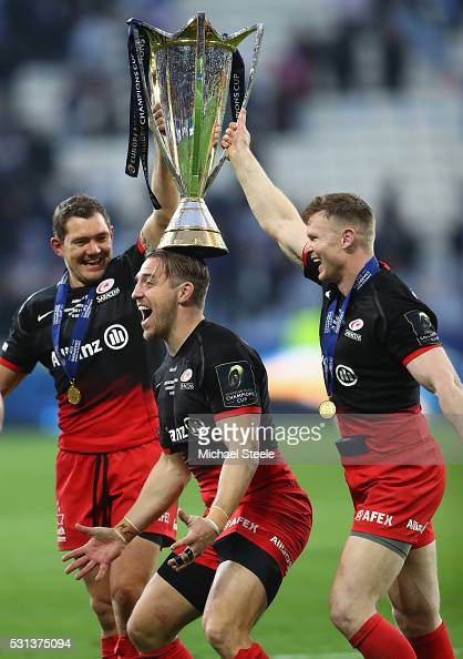 Alex Goode Chris Wyles and Chris Ashton of Saracens celebrate with the trophy after the European Rugby Champions Cup Final match between Racing 92...