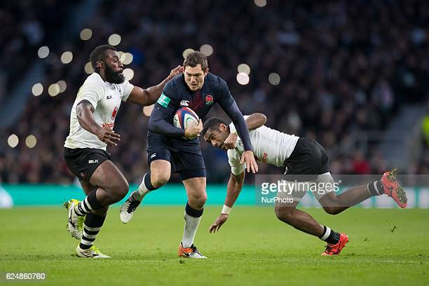 Alex Goode of England runs at Asaeli Tikoirotuma and Metuisela Tabebula of Fiji during Old Mutual Wealth Series between England and Fiji played at...