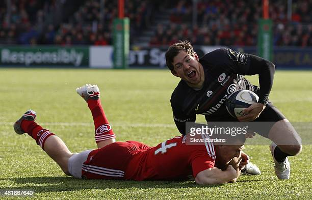 Alex Goode of Saracens is tackled by Andrew Conway of Munster during the European Rugby Champions Cup pool one match between Saracens and Munster at...
