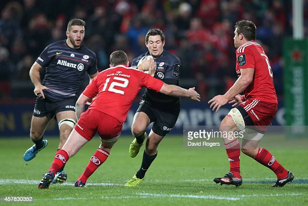 Alex Goode of Saracens is tackled by Denis Hurley and CJ Stander during the European Rugby Champions Cup match between Munster and Saracens at...