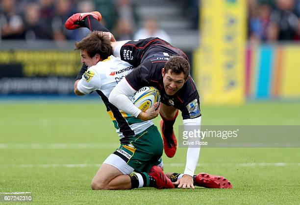 Alex Goode of Saracens is tackled by Lee Dickson of Northampton Saints during the Aviva Premiership match between Saracens and Northampton at Allianz...