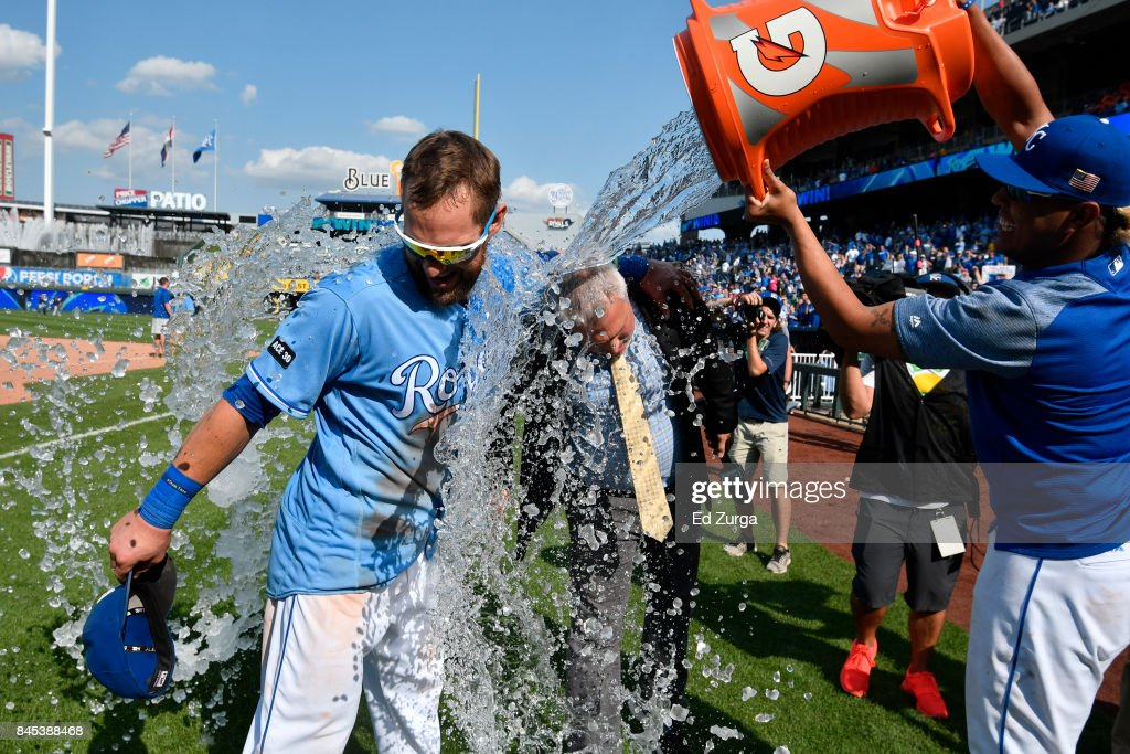 Alex Gordon #4 of the Kansas City Royals and Fox Sports' Joel Goldberg are doused with water by Salvador Perez #13 after a 11-3 win over the Minnesota Twins at Kauffman Stadium on September 10, 2017 in Kansas City, Missouri.