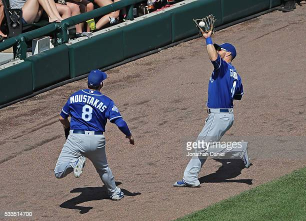 Alex Gordon of the Kansas City Royals catches a foul ball as Mike Moustakas charges towards him against the Chicago White Sox at US Cellular Field on...