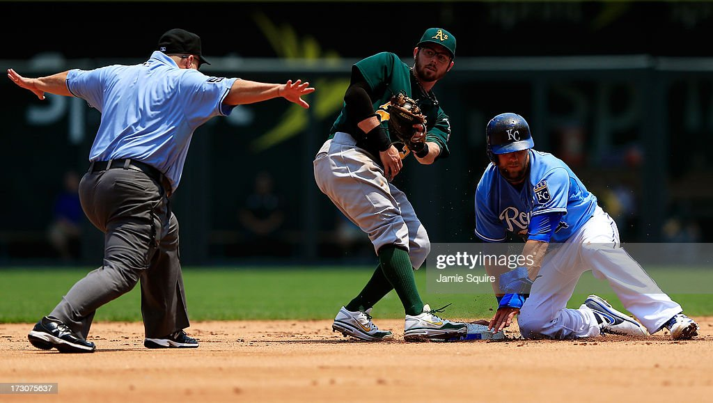 Alex Gordon #4 of the Kansas City Royals is called safe by umpire Eric Cooper #56 as Eric Sogard #28 of the Oakland Athletics is late applying the tag during the game at Kauffman Stadium on July 6, 2013 in Kansas City, Missouri.